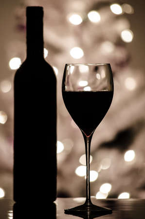 A red wine and bottle silhouette with blurred lights on Christmas tree in background  photo