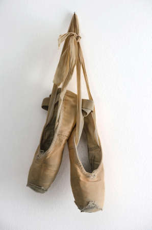 ballet shoes: Old used ballet shoes hanging from the wall.
