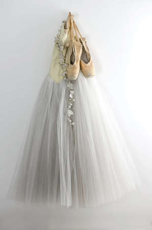 ballet slipper: Ballet dress and pointe shoes hanging on the wall
