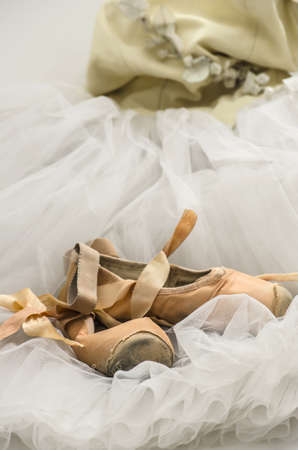 Old pointe shoes lying on a ballet dress  photo