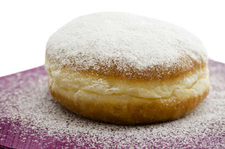 Donut on purple napkin with powdered sugar  Isolated on white  photo