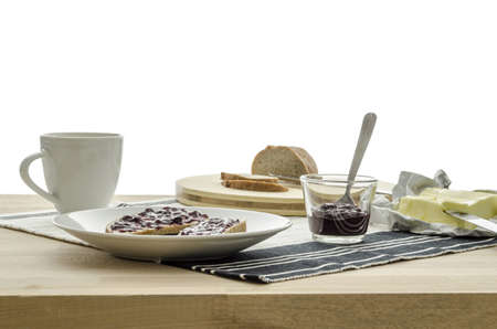 jam sandwich: Front view of  breakfast on wooden table with coffee, bread, jam and butter