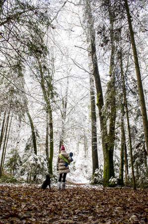mujer con perro: Madre con su bebé en un bosque Un perro está sentado a su lado y ella está esperando el camino cubierto de nieve Foto de archivo