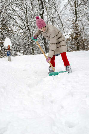 Young woman shoveling snow with green shovel  Stock Photo - 16828860
