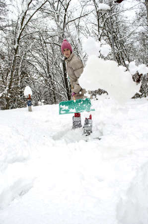 Young woman throwing snow in the air while shoveling  photo