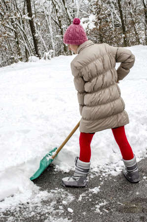 Young woman shoveling snow off street with green shovel  Stock Photo - 16828862