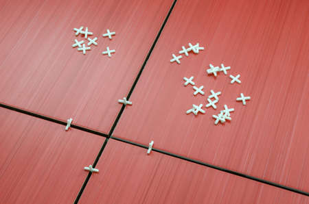 spread around: Closeup of unfinished red ceramic tiles with tile spacers spread around  Stock Photo