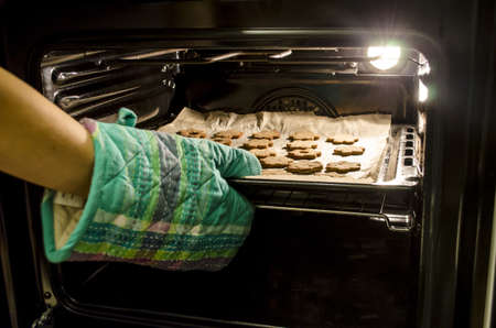 baking oven: Taking baked cookies out of the oven with kitchen gloves   Stock Photo
