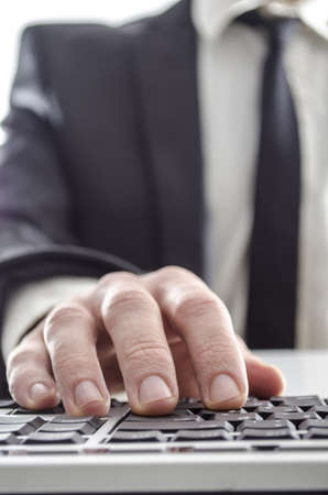 Closeup of a businessman using computer  His suit and tie in background   photo