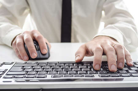 rat�n: Primer plano de un hombre usando la computadora de su camisa y corbata en fondo Foto de archivo