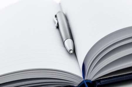 open diary: Black ballpoint pen lying on an open notebook