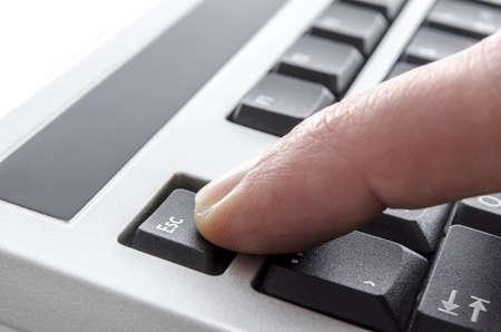 escape key: Closeup of a finger pushing escape key