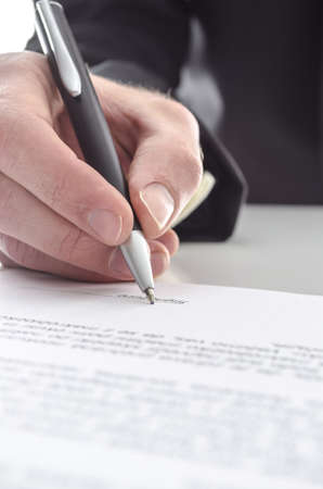 Cropped view of a businessman signing a contract  Shallow focus on signature   photo