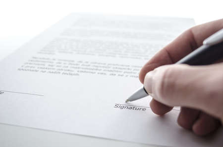 Male hand signing a contract above signature line  photo