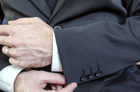 cuff links: Closeup of a businessman in black suit correcting a sleeve  Stock Photo