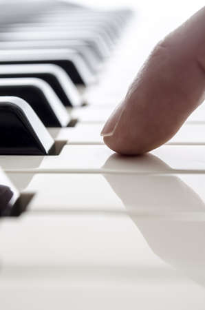 Detail of one male finger touching a piano key  photo