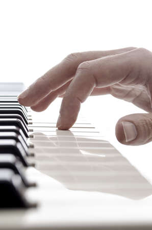 Isolated hand of pianist touching a key of electric piano with one finger  photo