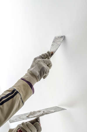 putty: Closeup of a man aligning a wall with spatula and trowel