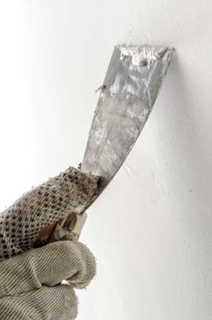 Detail of a male hand plastering  a wall with old spatula and putty  photo