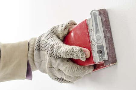 refurbish: Handyman working with sandpaper on a white wall