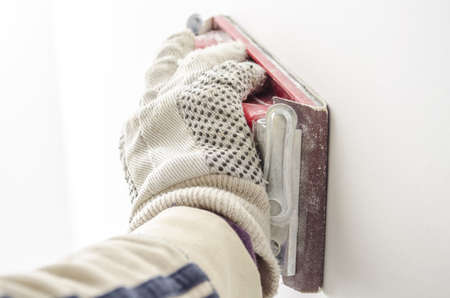 sidewall: Closeup of a male hand polishing a wall with sandpaper
