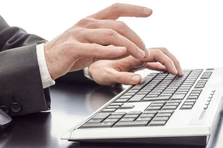Closeup of male hands typing on keyboard on a black table  photo