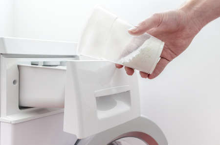 Closeup of a male hand filling detergent into the drawer of a washing machine  photo
