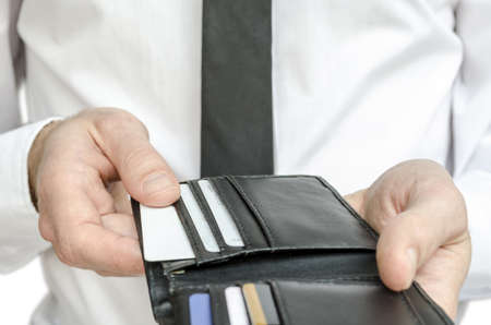 Man in white shirt and tie taking a credit card from a wallet  Stock Photo - 17195773