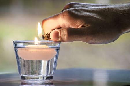 encendedores: Mano con una iluminación de una vela más ligera que flota en el agua Foto de archivo