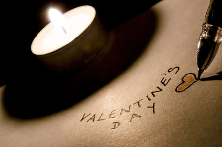 Writing a valentine text on a paper by a candlelight  photo