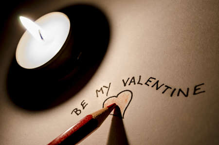 Pencil writing a Be my Valentine note- romantic scene with candle  photo
