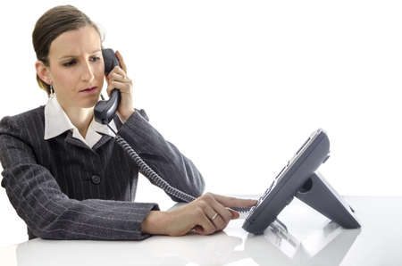 answering call: Young business woman sitting at office desk and using a phone  Stock Photo
