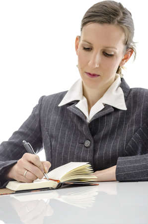 Business woman writing in her notepad on white office desk  Focus on a pen  Stock Photo - 17410781