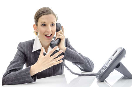 Enthusiastic woman at office desk talking on the phone  Isolated on a white background   photo