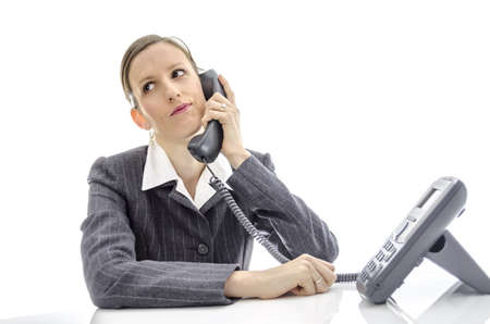 unmotivated: Impatient business woman at white desk making a phone call  Stock Photo