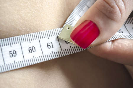 woman measuring: Detail of a woman measuring her waist with a tape measure