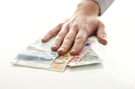 Man holding his hand over Euro money banknotes on a white table  Stock Photo - 17431094