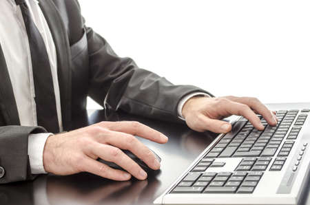 Closeup of a businessmans hands typing on keyboard on a black desk  photo
