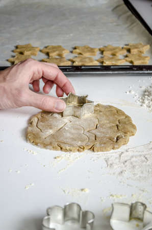 Photo of a mans hand making christmas cookies with cookie cutter  Stock Photo - 17508338