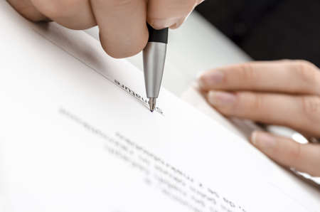 Detail of a female hand signing a contract above signature line  photo