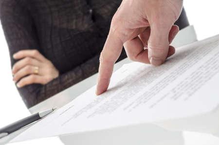 zeugnis: M�nnliche Hand zeigt eine Frau, wo ein Papier unterzeichnen