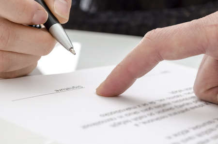witness: Detail of a woman signing a paper  Male finger showing where to sign