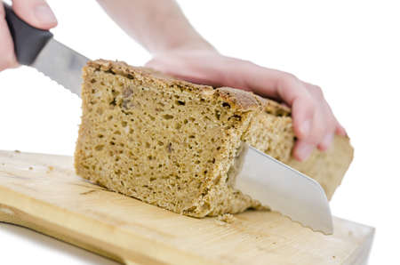 Cutting a homemade bread on a wooden board. Isolated over white background. Shallow dof. photo