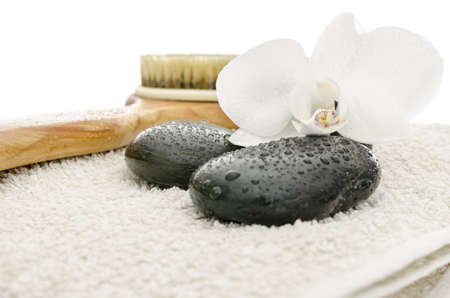 Wellness setting with massage stones, brush and white orchid flower on a towel  photo