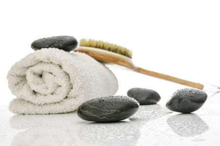 Spa and wellness setting with massage stones, brush and a towel  On a white table with water drops  Stock Photo - 17899364