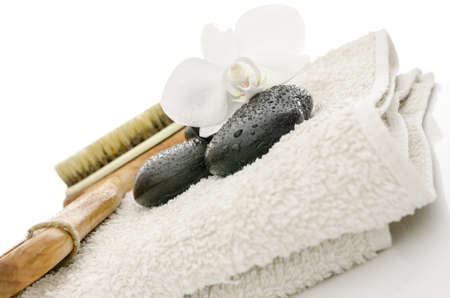 Spa setting with massage stones, brush, flower and a towel  With white background  Stock Photo - 17899367