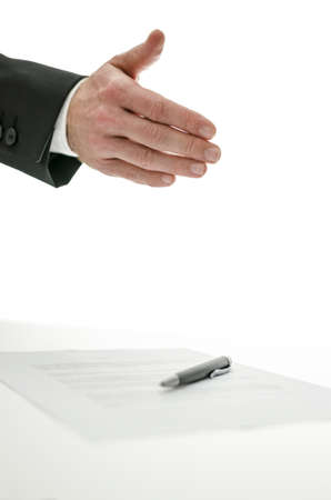 Business man offering a handshake over a signed contract   Isolated over white background  photo