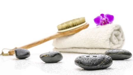 Spa setting with massage stones, brush and a towel  On a white table with water drops  photo