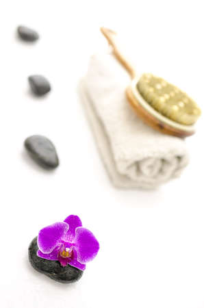 Spa setting with pink orchid and defocused massage stones, brush and a towel  photo