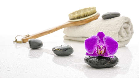 Wellness setting with violet orchid, spa stones, brush and towel  On a white table with water drops Stock Photo - 17997845